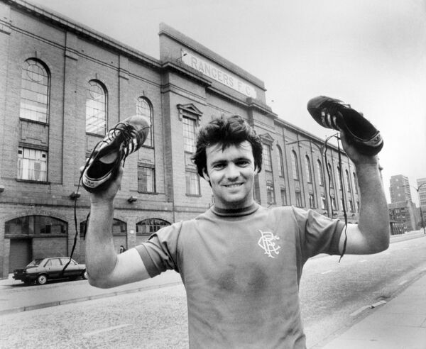 Rangers' Davie Cooper holds up his boots outside Ibrox
