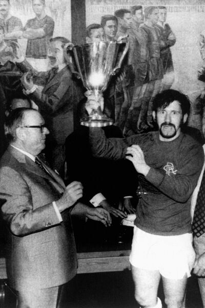 Rangers captain John Greig (c) lifts the European Cup Winners Cup after receiving it from UEFA President Gustav Wiederkehr (l)