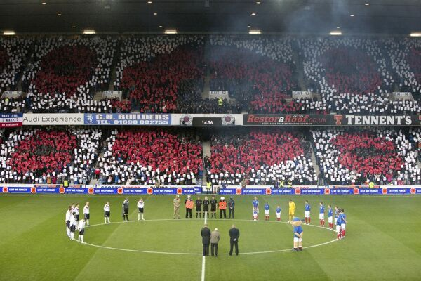 Rangers and Peterhead players observe the minute silence for Remembrance Day in front of the poppy card display by the fans