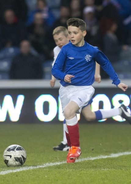 The Rangers soccer schools kids play on the pitch at half time